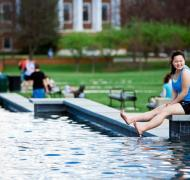 UMD female student sits on the edge of ODK Fountain with her feet dangling in the water