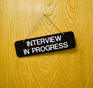"""Close up of a door with a sign saying """"Interview in Progress"""""""